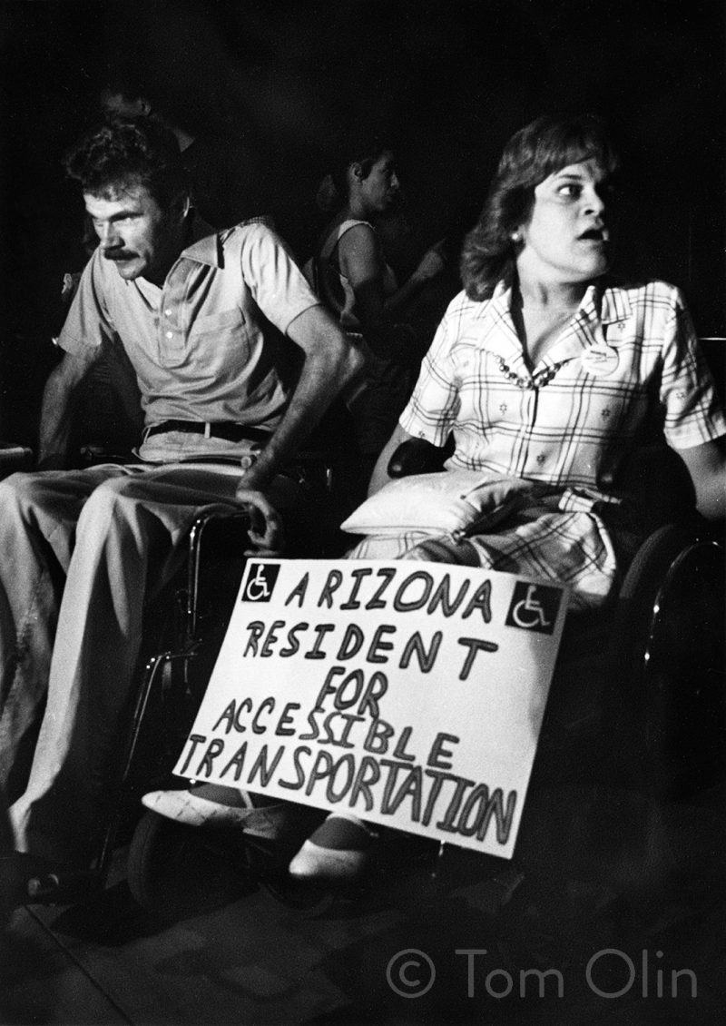 """Black and white photo of two people in wheelchairs. One is holding a sign that reads """"Arizona Resident for Accessible Transportation"""""""