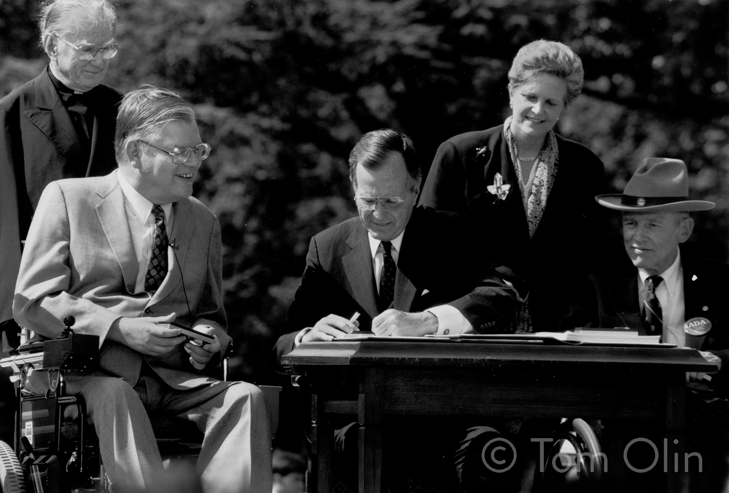 Black and white photo of the President signing a document with others smiling around him