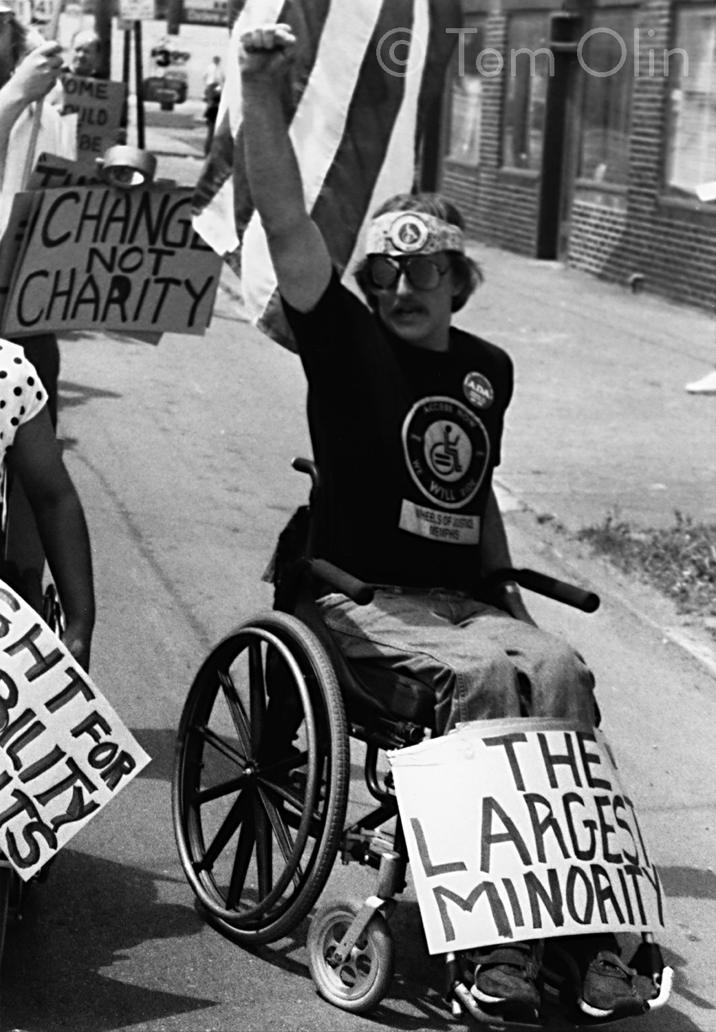 """Black and white photo of person in a manual wheelchair holding up their fist. A sign resting on their legs reads """"The Largest Minority,"""" a posting in the back reads """"Change not Charity"""""""