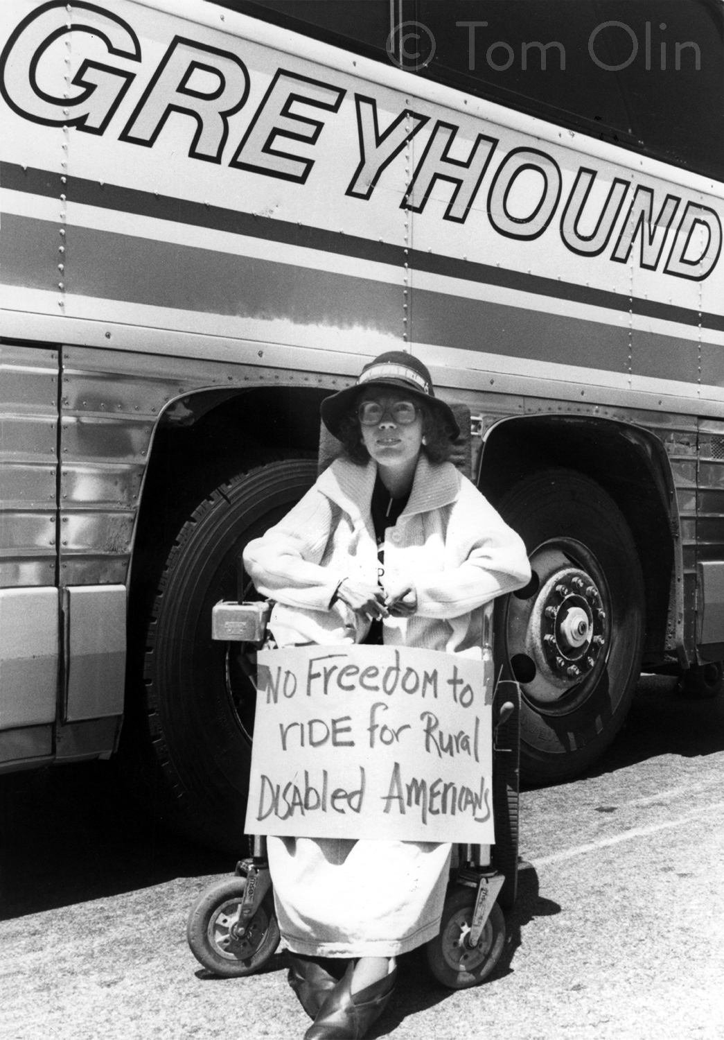 """Black and white photo of person wearing a sun hat and wearing a long coat sits in a power wheelchair with a sign that reads """"No freedom to ride for rural disabled americans."""""""