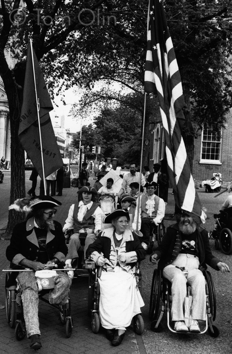 Black and white photo of three people in wheelchairs wearing period clothing and holding a U.S. flag, one with stars in the shape of the access symbol.