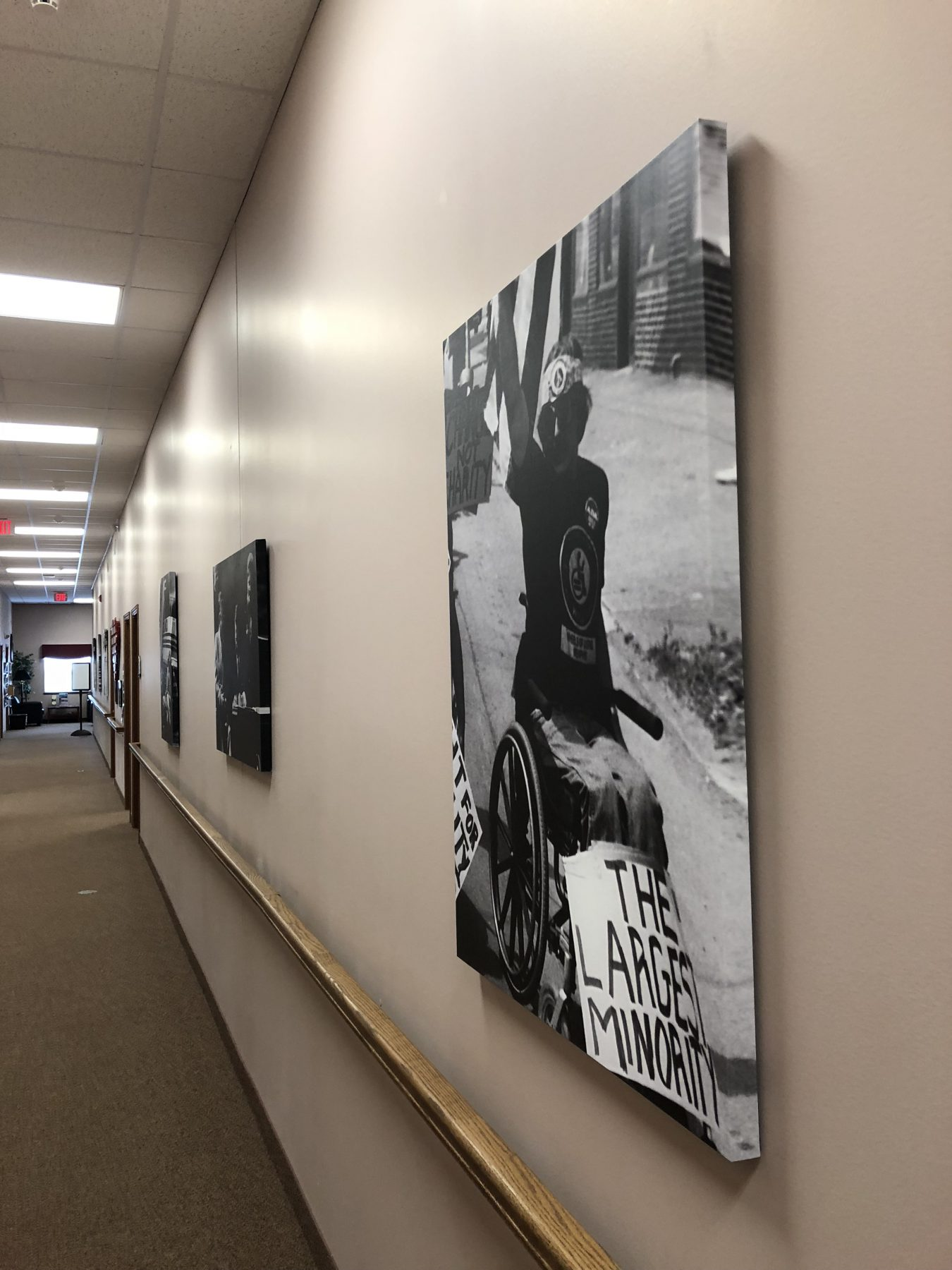 Office hallway with hand railing and Tom Olin's black and white photos hung on the wall
