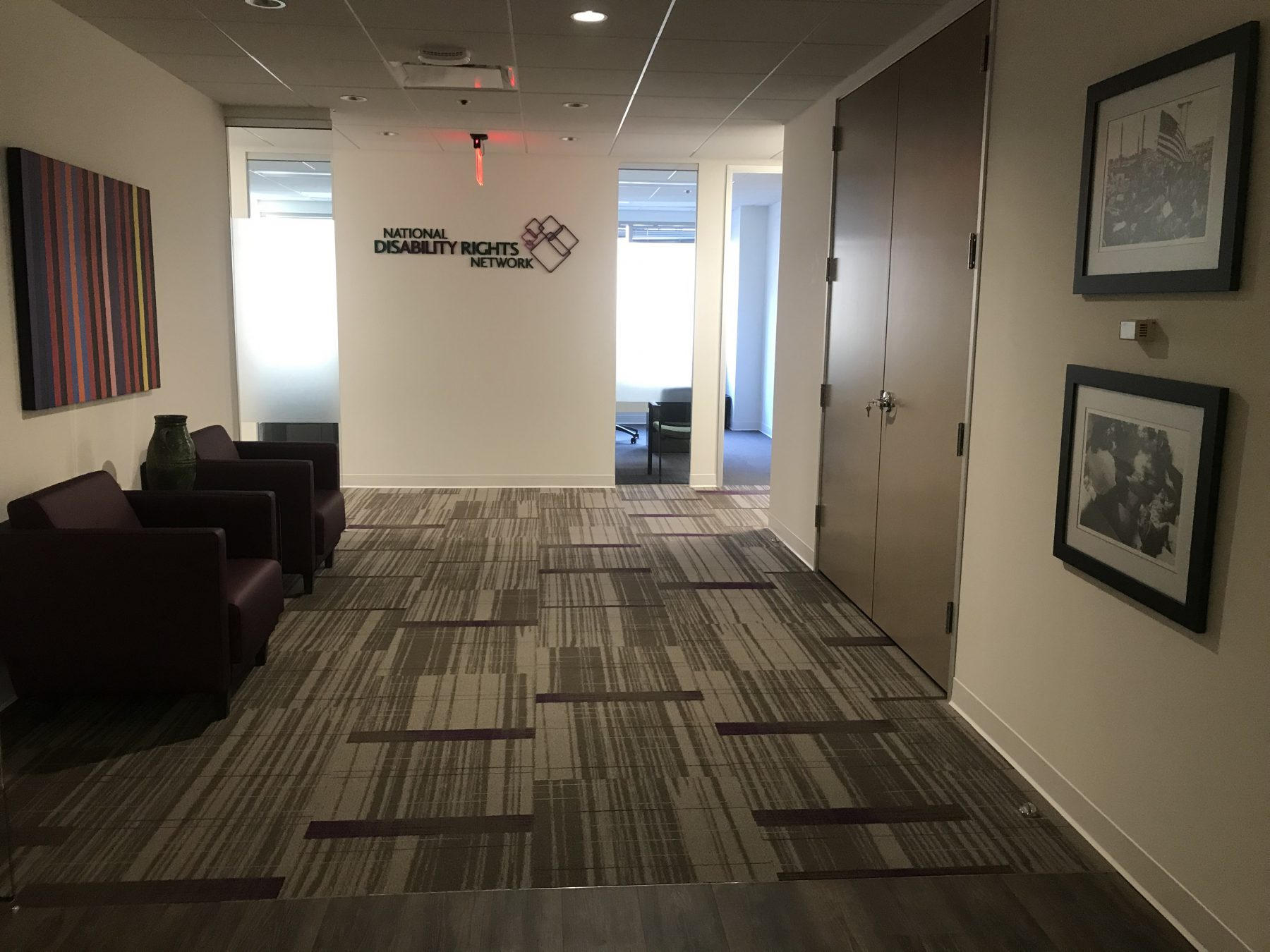 Lobby with the National Disability Rights Network logo on the wall and two Tom Olin black and white photos hung up