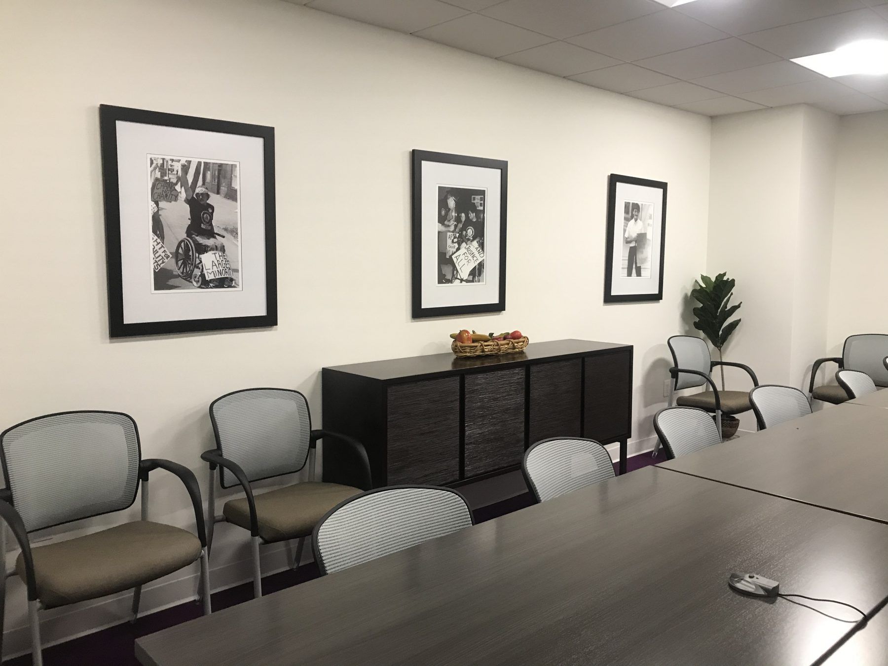 Meeting room with three black and white Tom Olin works hung in black frames