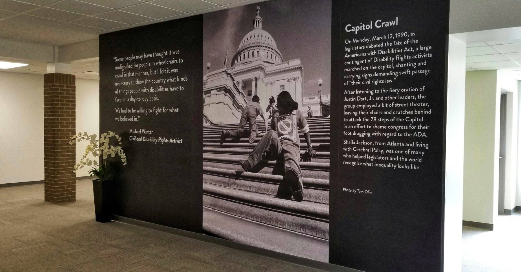 Interior hallway with Tom Olin's work - a large black and white photo of people crawling up the steps of the U.S. Capitol building in Washington, DC