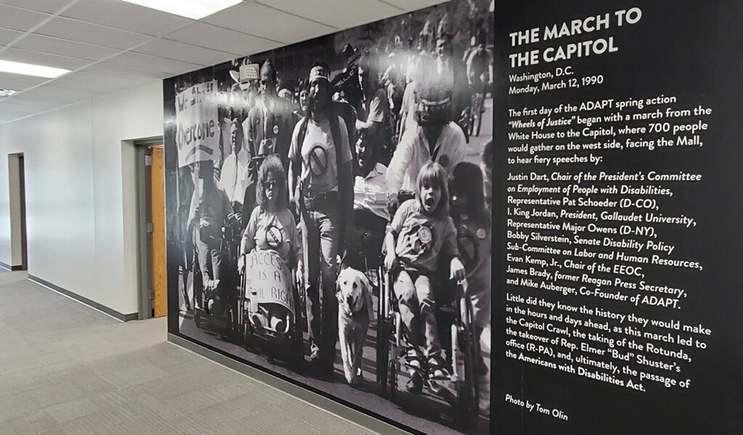 """Hallway with Tom Olin's work - a large black and white photo of people protesting"""""""